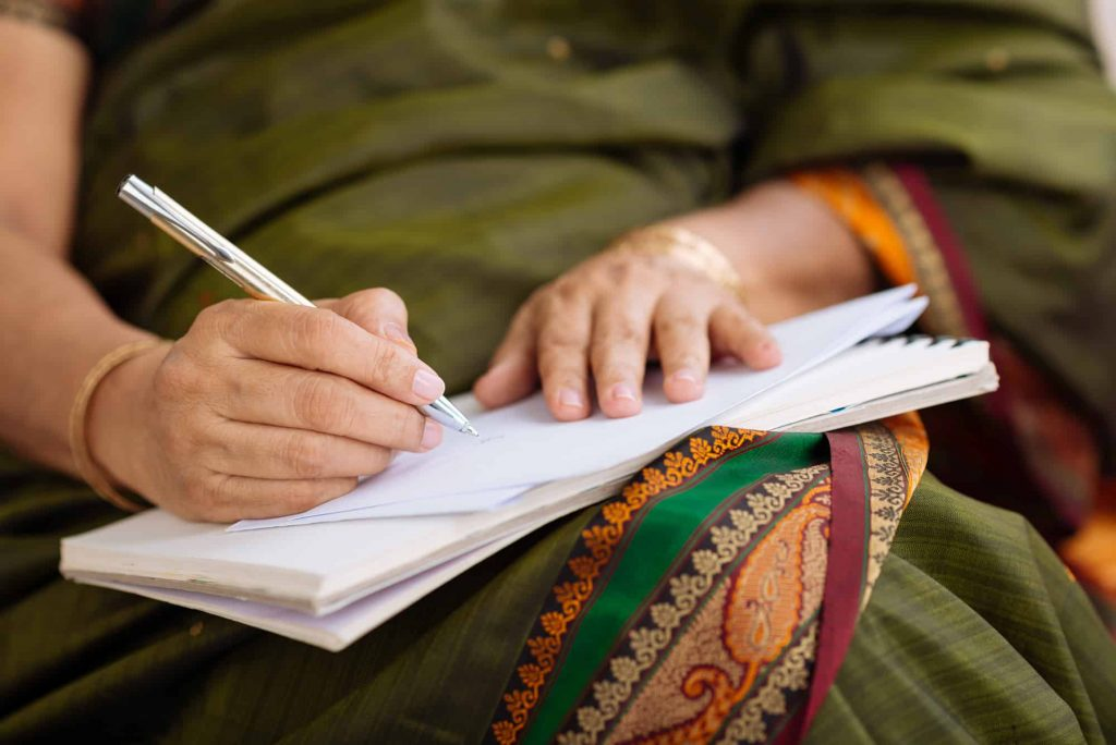 Image of persona writing in notebook: Things-To-Write-In-A-Journal