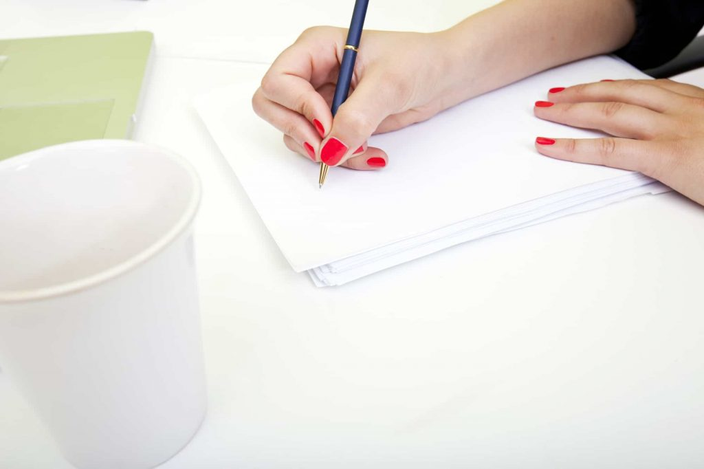 image of persons hand writing on paper example of things to write in a journal