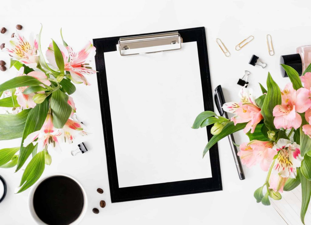image of clipboard and flowers for how to start a self care journal